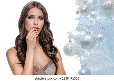 beauty portrait of attractive young caucasian woman brunette isolated on white studio shot lips face skin makeup long hair head and shoulders looking at camera hand nails christmas new year tree