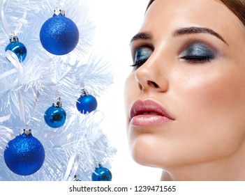 beauty portrait of attractive young caucasian woman brunette isolated on white studio shot  lips face closeup  skin makeup eyes closed christmas new year tree