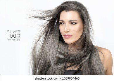 Beauty portrait of an attractive young woman with long trendy silver grey hair blowing around her face in a breeze isolated on white in a hair care and glamour concept