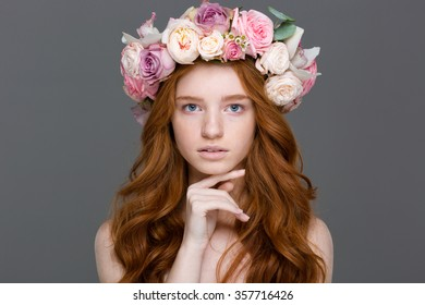 Beauty portrait of attractive young woman with curly red hair in flower wreath over grey background