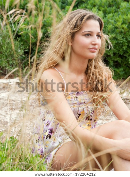 Beauty portrait of an attractive young woman relaxing in the dunes of a white sand beach with the wind blowing her hair enjoying a summer holiday and being thoughtful. Outdoors healthy lifestyle.
