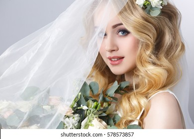 Beauty portrait of a beautiful blonde bride in veil with a bouquet of flowers in his hands on a gray background.