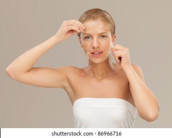beauty portrait of beautiful blonde woman peeling off a facial mask, smiling