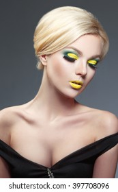 Beauty portrait of a beautiful blonde with yellow makeup on a gray background