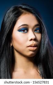 Beauty Portrait. Beautiful brunette Asian woman with long black hair. Shot in a studio on a black background