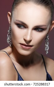 Beauty portrait of a beautiful girl with evening make-up and elegant earrings.