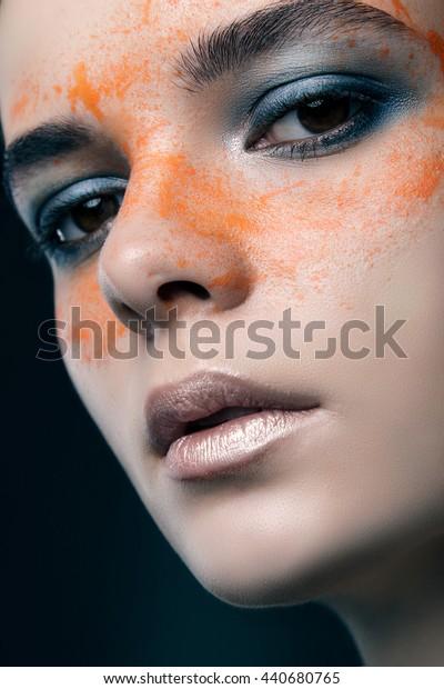 beauty portrait of a beautiful girl with orange eye drops. fashion portrait