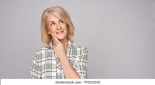 beauty portrait of beautiful middle age woman looking up and thinking. Isolated on grey with copy space