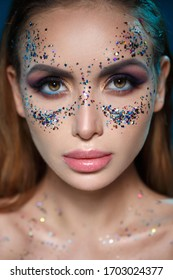 Beauty portrait of a beautiful sexy girl with bright makeup and sparkles in the shape of a mask on her face.