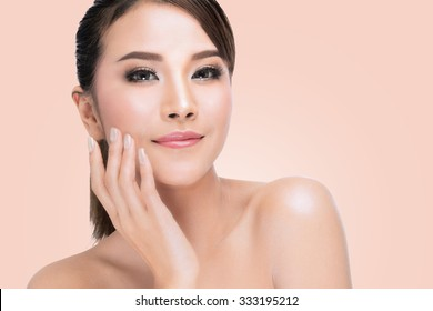 Beauty Portrait. Beautiful Spa Asian Woman Touching her Face. Perfect Fresh Skin. Pure Beauty Model. Youth and Skin Care Concept. on pink background with clipping path