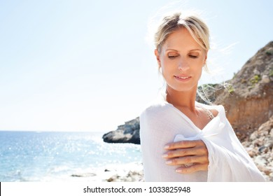 Beauty portrait of beautiful tourist woman relaxing on sunny holiday beach with white fabric wrapped around her, serene contemplative in nature outdoors. Healthy wellness leisure recreation lifestyle.