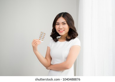 Beauty portrait of a beautiful young woman with pills.