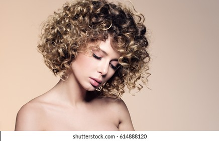 Beauty portrait of beautiful young woman with closed eyes. Hairstyle with curly hair. Professional make-up, delicate clean skin. Neutral beige background with free space