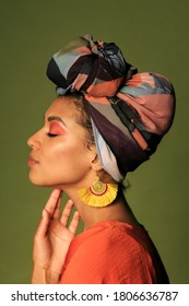 Beauty portrait of Black African American woman in  orange clothing and ethnic head wrap  i poing in studio. Bright make up.