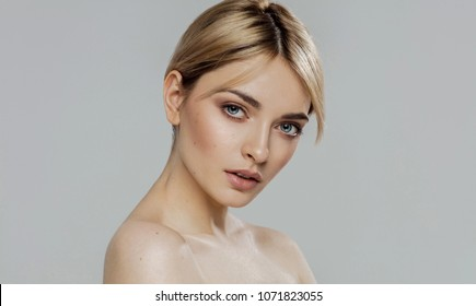 Beauty portrait of blond female model isolated on grey background