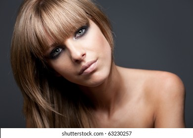 Beauty portrait of a blond woman with naked?shoulders?on blue background, head tilted on the left side