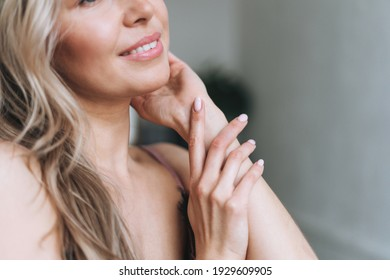 Beauty portrait of blonde smiling woman 35 year plus clean fresh face and hands with light pink manicure