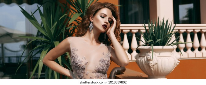 Beauty portrait of bride wearing fashion wedding dress with feathers with luxury delight make-up and hairstyle, Italian lake ,spring photo. Young attractive multi-racial Asian Caucasian model.
