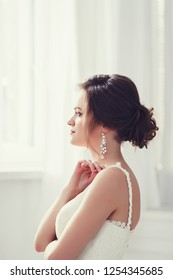 Beauty portrait of bride wearing fashion wedding dress with luxury hairstyle, studio indoor photo.