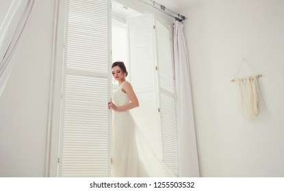 Beauty portrait of bride wearing fashion wedding dress make-up and hairstyle, studio indoor photo.