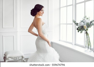 Beauty portrait of bride wearing fashion wedding dress with feathers with luxury delight make-up and hairstyle, studio indoor photo. Young attractive multi-racial Asian Caucasian model. Serious