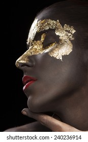 Beauty portrait of a brown-skinned girl with golden makeup of foil red lips
