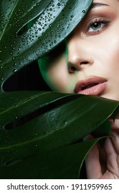 Beauty Portrait of brunette girl in palm leaves. Beautiful young woman with Make-up. Natural cosmetics concept