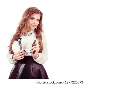 Beauty portrait of brunette Latin American woman with rulers and tattoo machine in hands isolated on white background. Eyebrows micro-pigmentation specialist in formal wear posing looking at camera ha