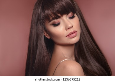 Beauty portrait of brunette woman with eyeliner makeup and long healthy shiny hair style isolated on brown posing in studio.