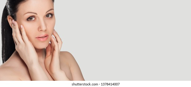 Beauty portrait of brunette woman with natural glowing skin. Skin care concept. Healthcare. Banner, copy space.