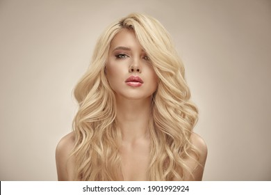 Portrait de beauté d'une femme caucasienne aux cheveux bouclés blonds sur fond beige isolé