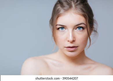 Beauty portrait of a charming woman with blue eyes looking at camera over gray background
