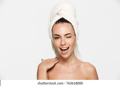 Beauty portrait of a cheerful attractive half naked woman with a towel wrapped around her head winking and looking at camera isolated over white background