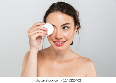 Beauty portrait of a cheerful young topless woman removing face make-up with a cotton pad isolated over gray background