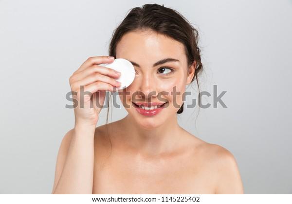 グレイの背景に綿パッドと化粧を取り除く明るい若いトップレスの女性の美しいポートレート