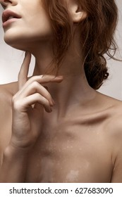 Beauty portrait of chestnut-haired girl with long neck and distinctive collar bones, long fingers touching chin and piebald skin
