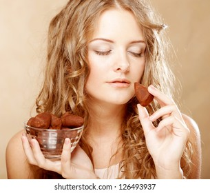 beauty portrait of a cute blond girl in act to eat a chocolate candy