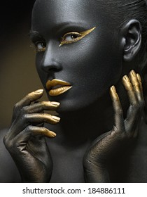 beauty portrait of a dark-skinned girl with golden makeup