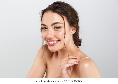 Beauty portrait of a delighted young topless woman with make-up applying body cream isolated over gray background