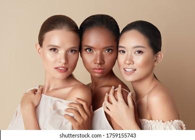 Schönheit. Portrait von Models der Vielfalt. Mixed Race, asiatische und kaukasische Mädchen umarmt einander und sehen sich die Kamera an. Unterschiedliche ethnische Frauen mit Aktkonfektion und perfekter blühender Haut.