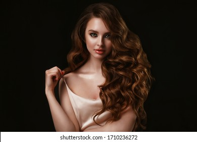 Beauty portrait of elegant young woman. Glamour makeup. Face of the beautiful woman with long brown curly hair posing at studio over dark background. Sensual portrait.