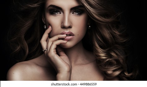Beauty portrait of elegant young woman. Dark background. Girl looking at camera. Glamour makeup. Naked shoulders. Ideal skin.