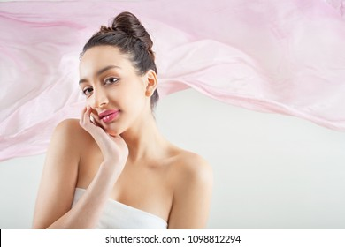 Beauty portrait of ethnic asian young woman with perfect flawless skin looking smiling, pink floating fabric background, studio indoors. Cosmetics healthy beautiful female, dreamy ethereal lifestyle.
