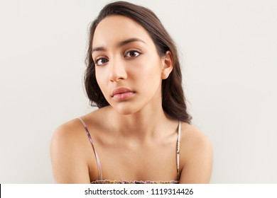 Beauty portrait of ethnic asian young woman with healthy hair and skin looking at camera against a plain white background, indoors. Wellness flawless skin care, beautiful female, youth lifestyle.