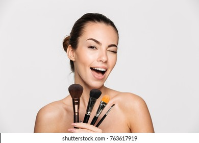 Beauty portrait of an excited beautiful half naked woman holding set of make-up brushes and winking isolated over white background