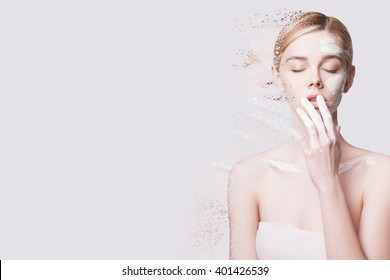 Beauty Portrait Face Scrub, Crumbled into Small Pieces, Scrubs on a Woman's Face. Anti-Aging Facials. Young Woman Applies a Mask to the Face, she Crumbles into Small  Particles on a light Background