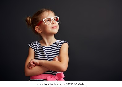 Beauty portrait of fashion girl wearing spectacles looking up over studio background. Cute child dreaming about future.