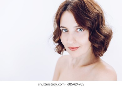 Beauty portrait of female with curly hair and natural skin. Selective focus. White background with copy space. Spa girl