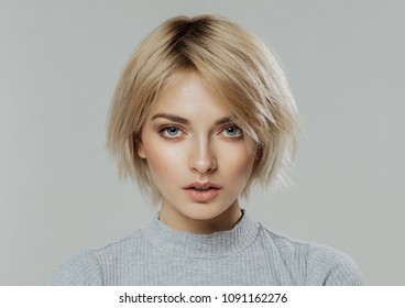 Beauty portrait of female face with natural skin looking at camera isolated on grey
