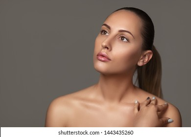 Beauty portrait of female face with natural perfect skin. model with light nude make-up on dark background
